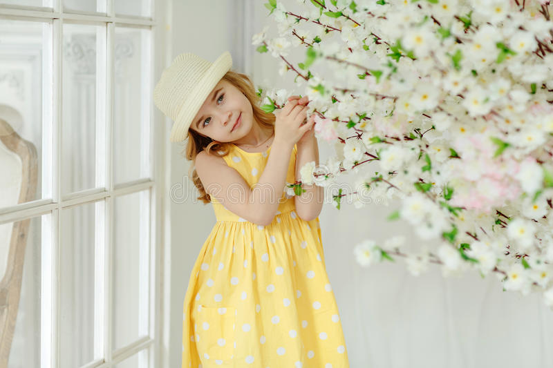 Charming little girl blonde in a hat and yellow dress in a light royalty free stock photo
