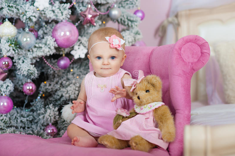 Charming little girl with blue eyes sitting in a pink armchair teddy bear on background decorated Christmas tree. Cute baby girl sitting under christmas tree in stock images