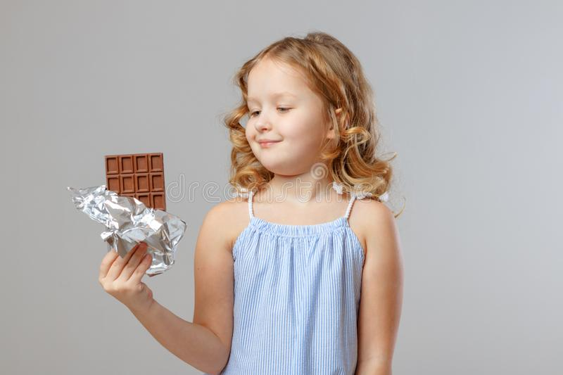 Charming little girl child blonde looks at a bar of chocolate. Gray background, studio, portrait royalty free stock photography