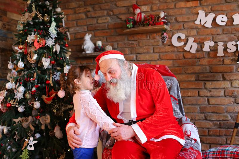 Little girl hugs Santa Claus and makes wish for Christmas in coz. Charming little girl comes to Christmas grandfather who sits on large armchair and whispers in stock images