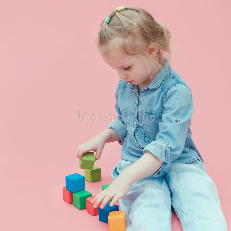 A charming little girl in denim clothes on a pink background plays with wooden colored cubes. stock images