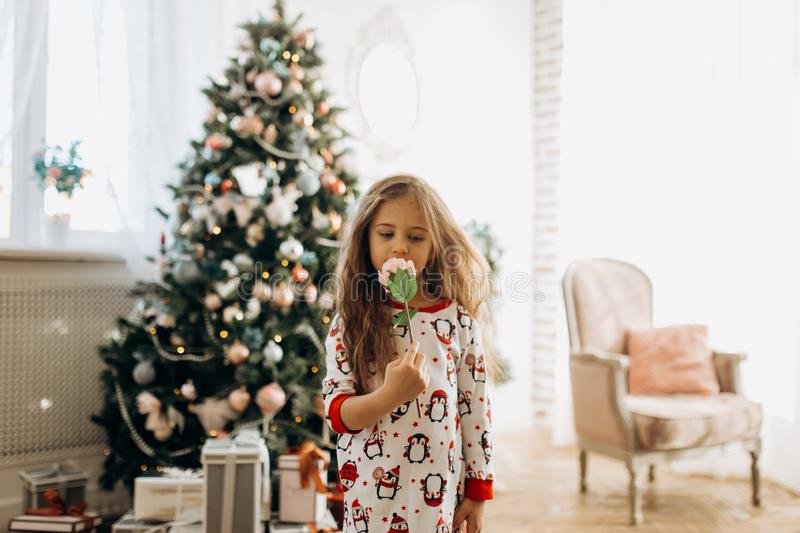 Charming little girl dressed in pajama holds a flower in the full of light cozy room with the New Year`s tree stock image