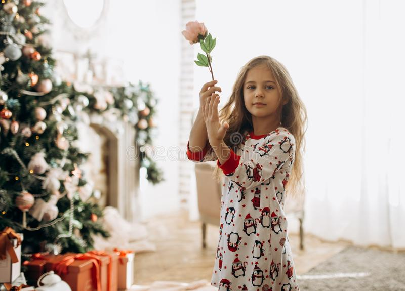 Charming little girl dressed in pajama holds a flower in the full of light cozy room with the New Year`s tree stock photography