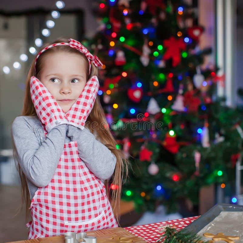 Charming little girl in gloves baking Christmas stock photo