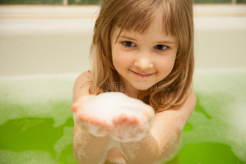 Charming little girl has a bath royalty free stock image