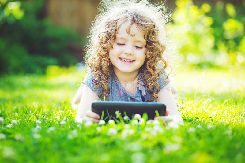 Charming little girl lying on the grass and holds in hands tablet. Charming curly girl lying on the grass and holds in hands tablet stock photography