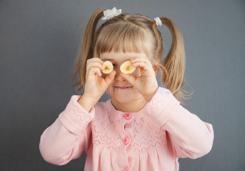 Charming little girl playing with pieces of a ripe banana royalty free stock images