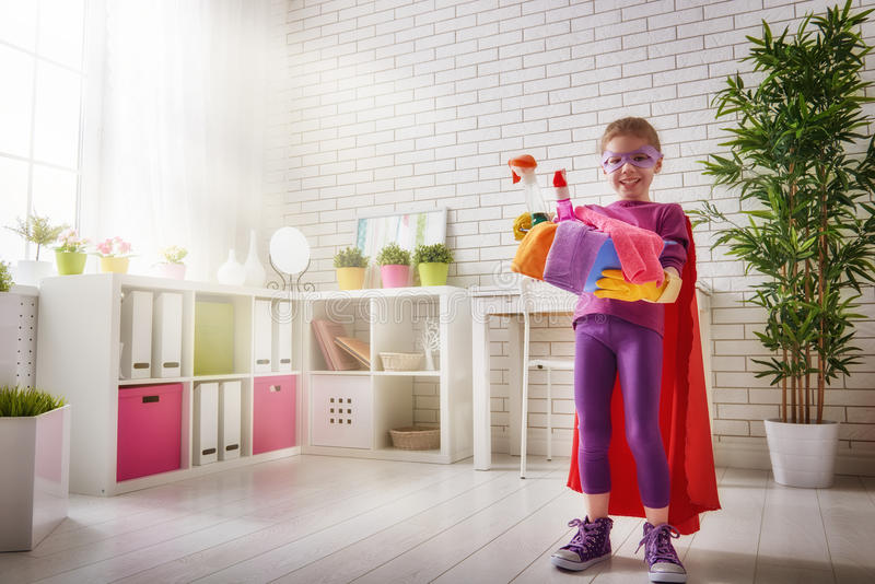 Charming little helper. Cute little child girl makes cleaning the house. Girl is dressed in a Superman costume royalty free stock photo