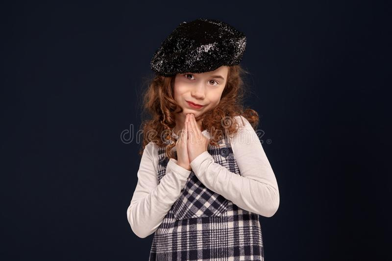 Stylish brunette kid is posing in studio on a black background. Children`s fashion. stock photography