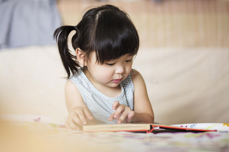 Charming and lovely asian kid concentrated on reading book.  royalty free stock images