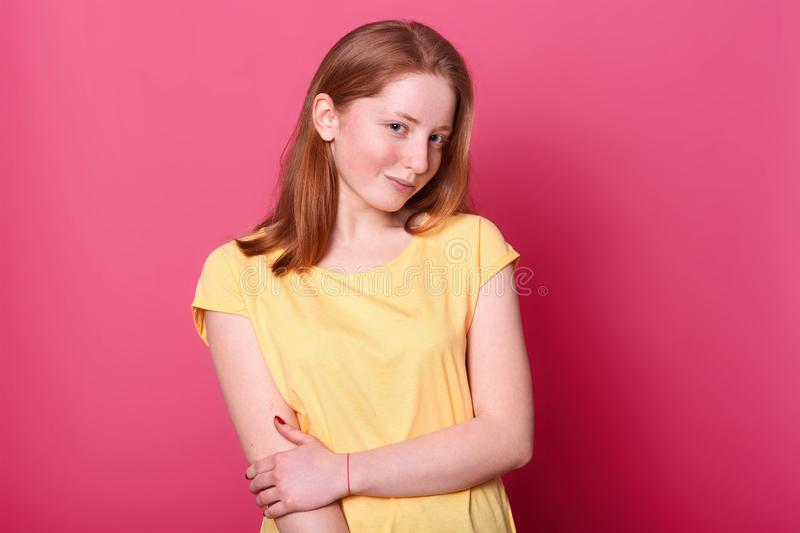Charming magnetic positive girl poses isolated over bright pink background in studio, holding her arm, looking mysterious at stock image