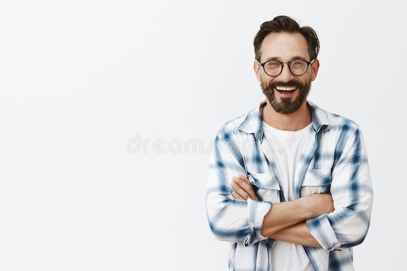 Charming male professor of university standing over gray background in stylish sunglasses and checked shirt, talking stock image