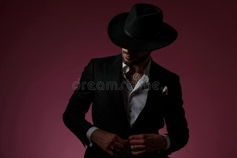 Charming man unbuttoning his shirt and looking away royalty free stock image