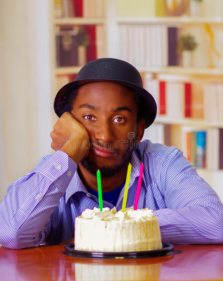 Charming man wearing blue shirt and hat sitting by table with birthday cake in front, looking sad depressed celebrating. Alone royalty free stock photo