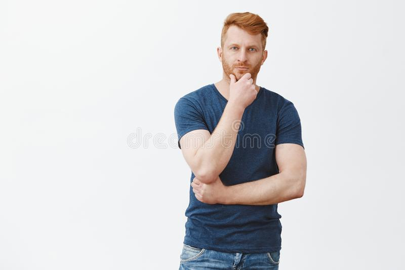 Charming masculine redhead man in blue t-shirt, touching beard and gazing at camera with thoughtful look, thinking stock photos