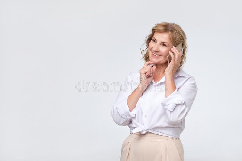 Charming mature caucasian lady in white shirt speaking by phone with client stock photo