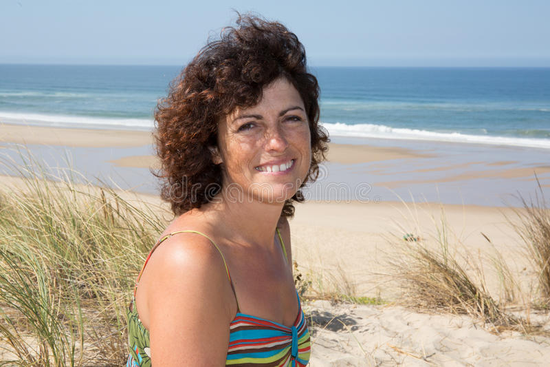 Charming middle-aged brunette woman on the beach royalty free stock photos