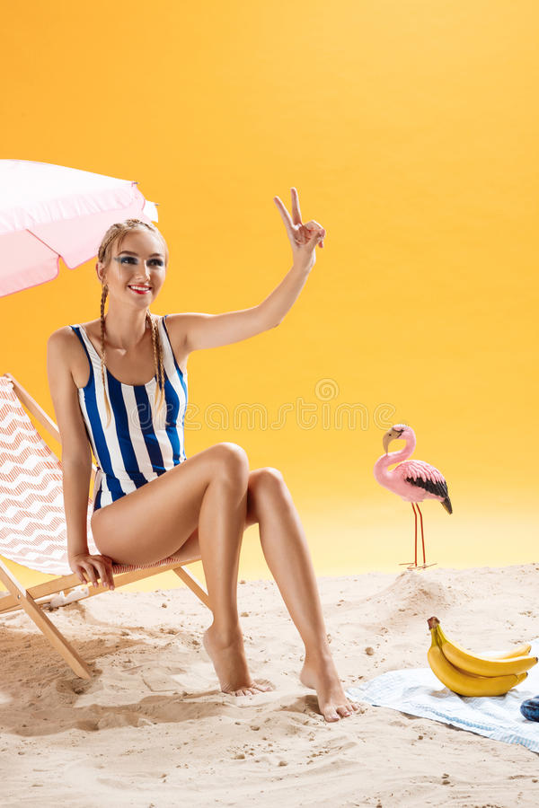 Charming model girl on beach showing peace sign looking away. Model girl with cool hairstyle and tanned skin on beach showing peace sign looking away royalty free stock photography