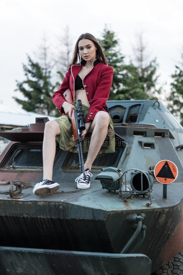 Charming model with the gun sitting on the tank. Charming model with the gun sitting on the tank stock photos