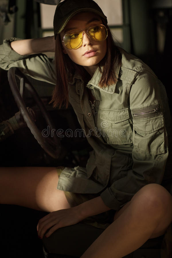 Charming model sitting in the army tank. stock photo