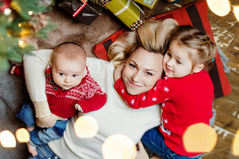 Charming mother blonde in white sweater hugs her daughter and to stock photos