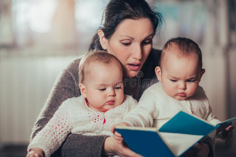 Charming mother showing images in a book to her cute twin babies stock photo