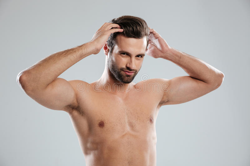 Charming naked bearded man posing and touching his hair stock photos