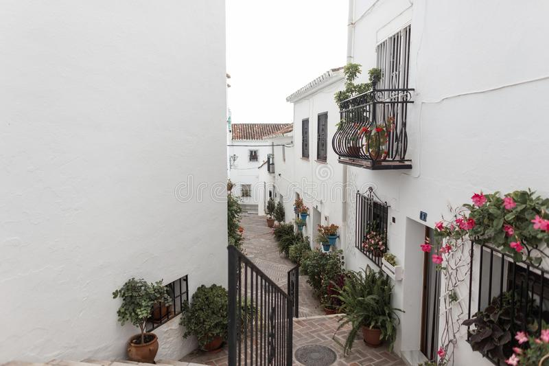 Charming narrow old streets of a white village with vintage balconies and with pink flowers in pots on the facades of houses. Small town in Spain royalty free stock photos