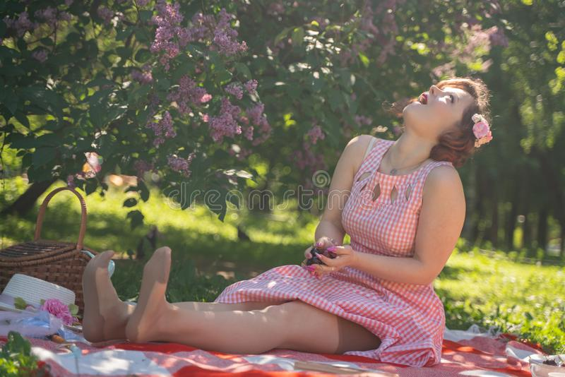Charming pinup girl enjoys a rest and a picnic on the green summer grass. pretty vintage style caucasian woman spend vacantion on. City park alone. fun stock images