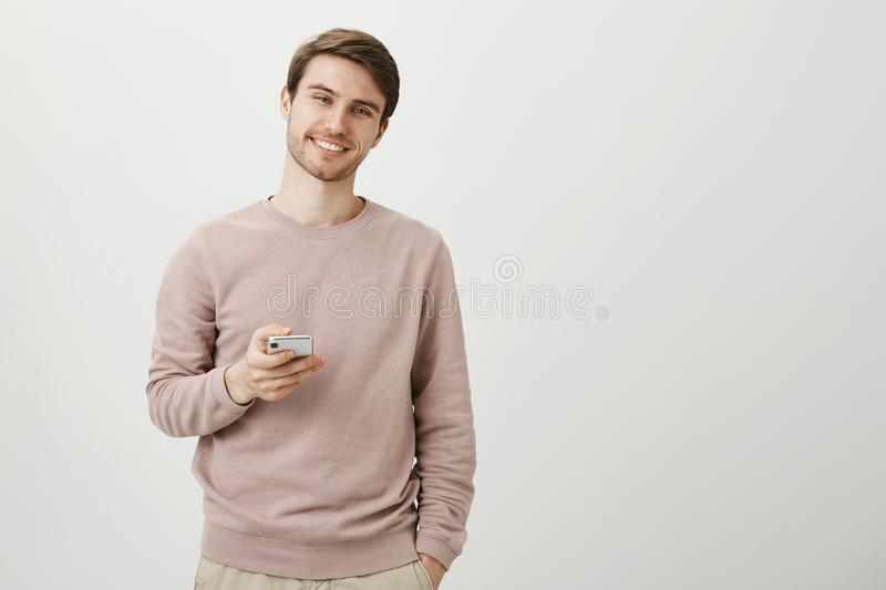 Charming pleasant young unshaven man standing with cute smile, holding smartphone and looking at camera while being over. Gray background. Guy chit-chat with stock photos