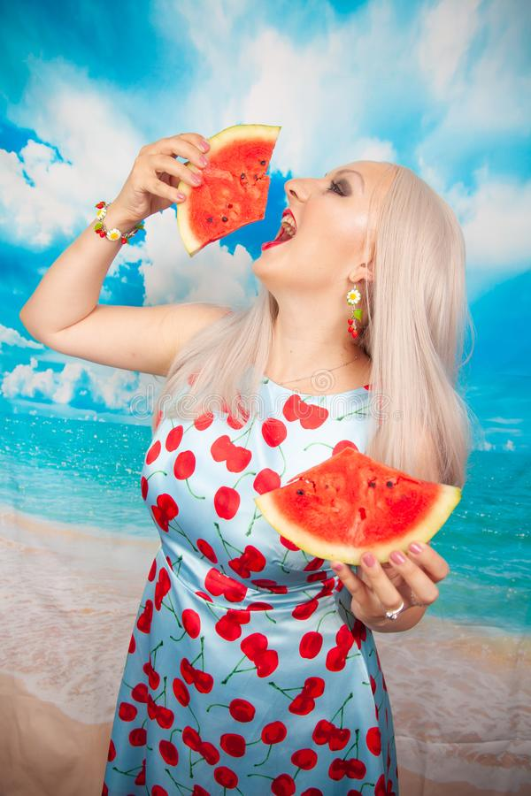 Charming plump blonde in blue pin up dress stands with a piece of watermelon and enjoys rest and a snack. Charming plump blonde with big Breasts in a swimsuit stock photography