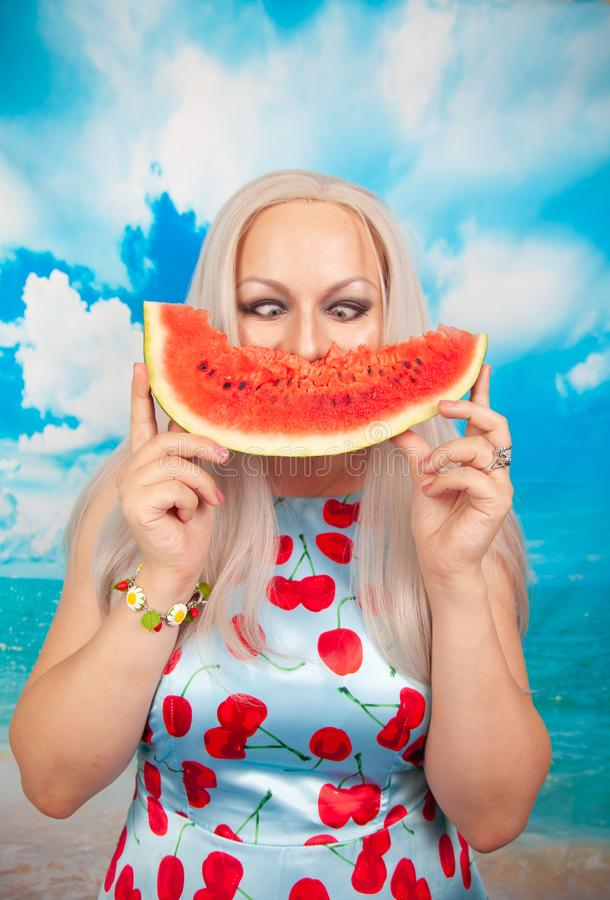 Charming plump blonde in blue pin up dress stands with a piece of watermelon and enjoys rest and a snack. Charming plump blonde with big Breasts in a swimsuit royalty free stock images