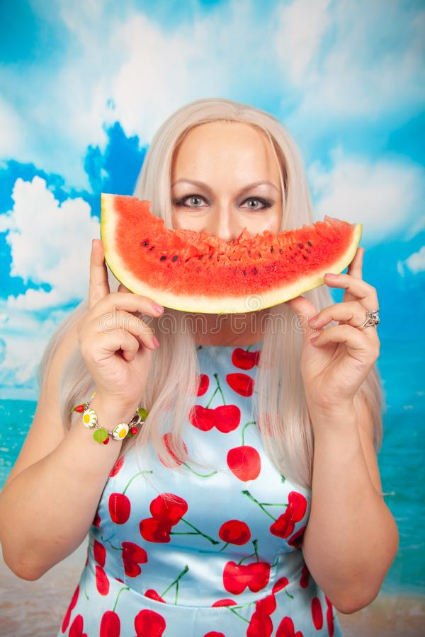 Charming plump blonde in blue pin up dress stands with a piece of watermelon and enjoys rest and a snack. Charming plump blonde with big Breasts in a swimsuit royalty free stock photos