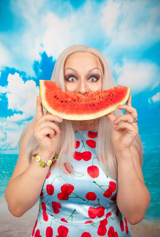 Charming plump blonde in blue pin up dress stands with a piece of watermelon and enjoys rest and a snack. Charming plump blonde with big Breasts in a swimsuit royalty free stock image