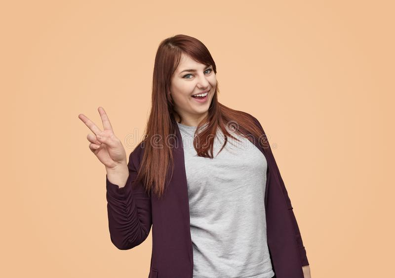 Charming plump girl showing two fingers stock images