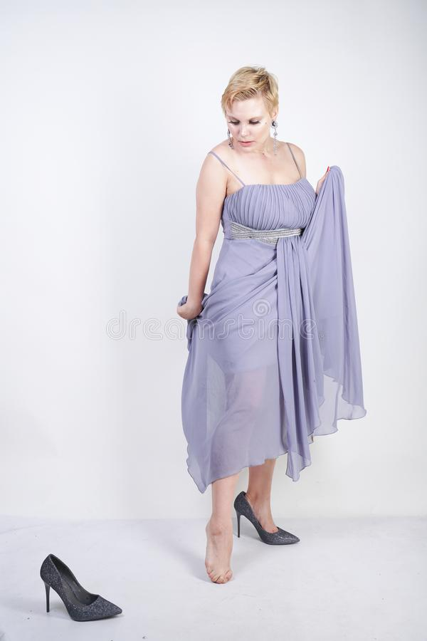 Charming plus size young woman in grey gown dress lost slipper on white background in Studio. beautiful chubby short hair blonde g stock photos