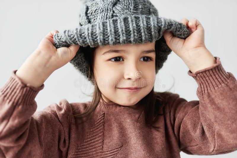 Charming portrait of Caucasian little girl playing with the winter warm gray hat, smiling and wearing sweater isolated on a white royalty free stock images