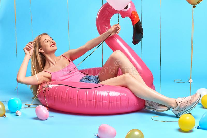 Charming positive happy girl lying on the inflatable mattress stock photography