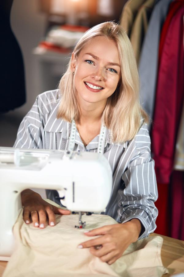 Charming positive woman repairing clothes in the room. royalty free stock photo