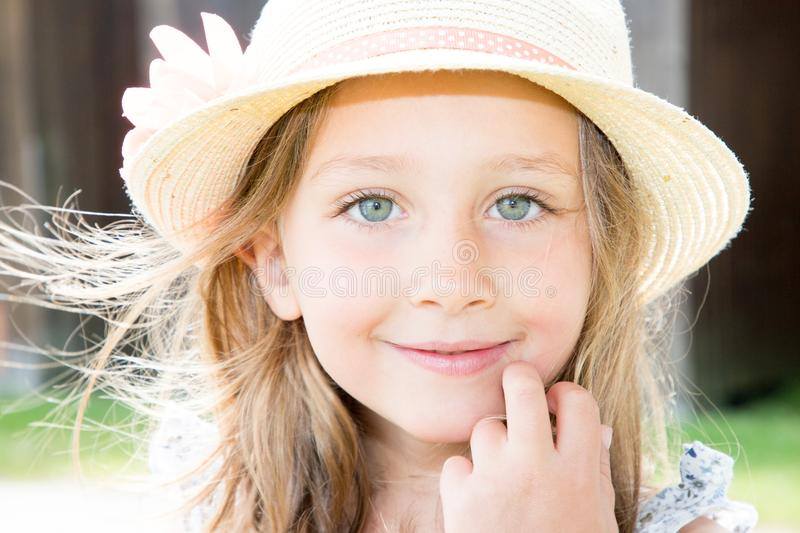 Charming preschool girl with big blue eyes and long loose blonde hair wearing straw hat looking at camera with hand finger on her royalty free stock images