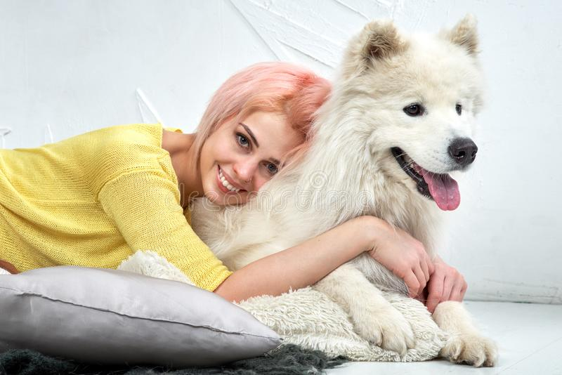 Charming pretty girl looking at camera and hugs her dog, young woman smiles widely and shows beautiful white teeth. stock photos