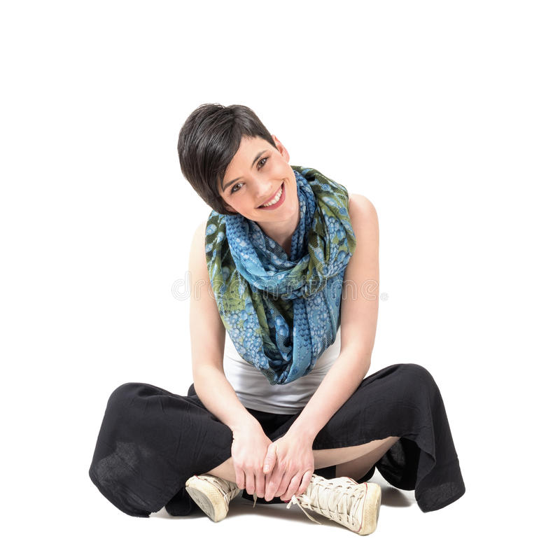 Charming pretty girl sitting cross-legged smiling at camera with slanted head stock images