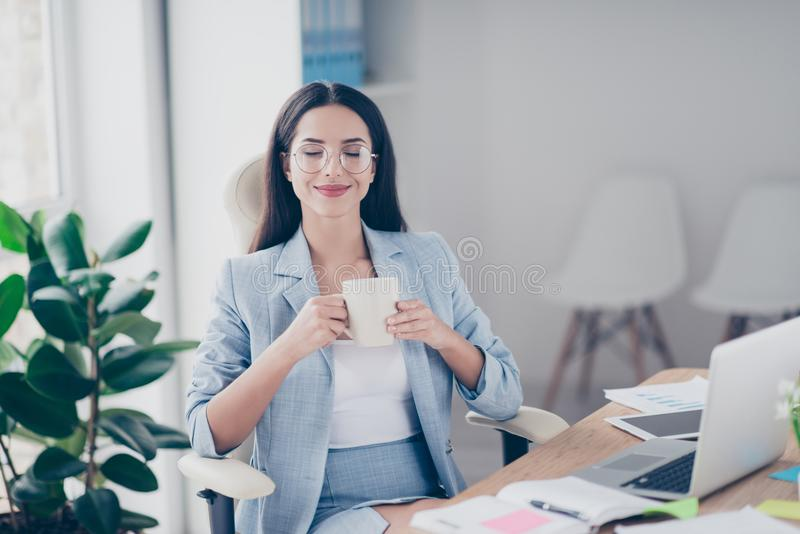 Charming, pretty, nice, cute financier sitting in workstation ho. Lding mug of tea, with close eyes enjoying coffee time in the morning, perfect start of working stock image