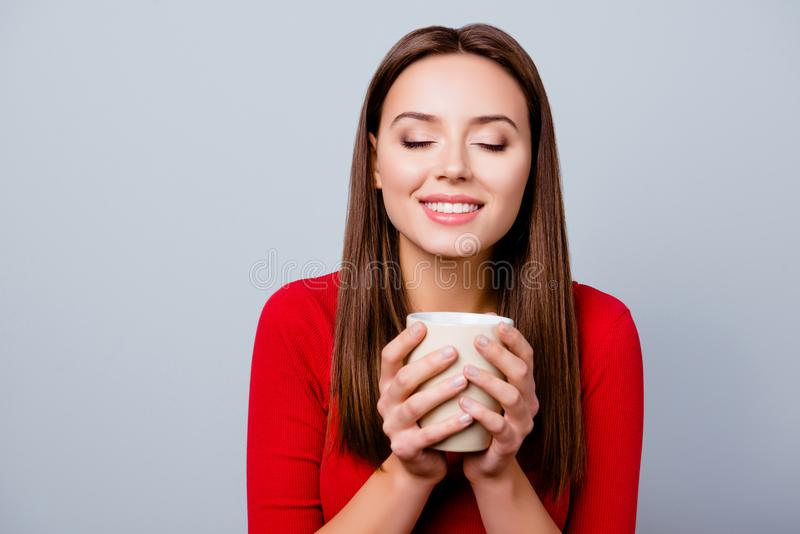 Charming, pretty, nice, cute, lovely woman in casual outfit, having cup of beverage in hands, enjoying smell with close royalty free stock image