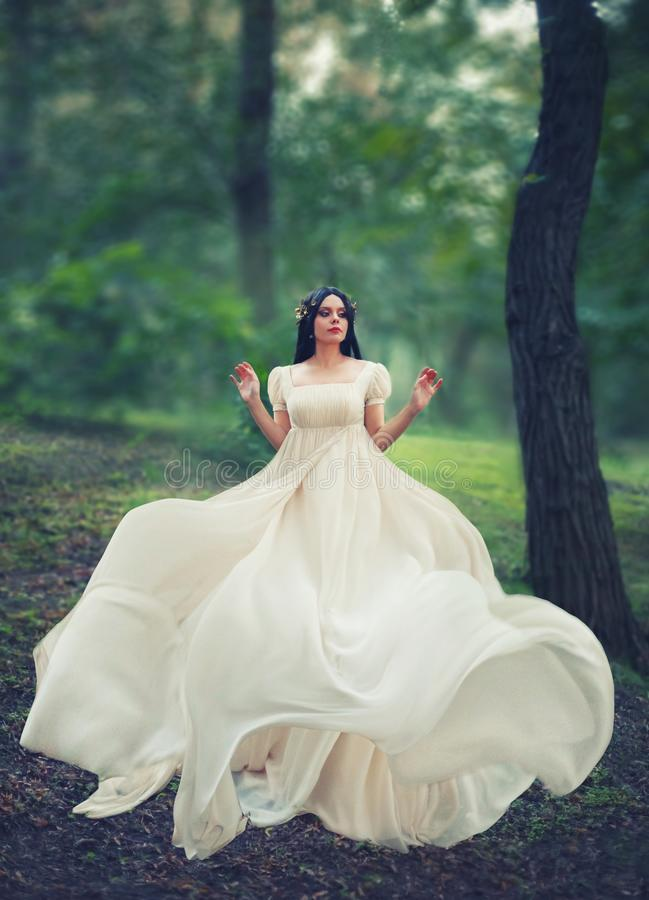 Charming princess in a bright green forest dances alone, dark-haired girl in long white elegant gentle dress with flying royalty free stock photos