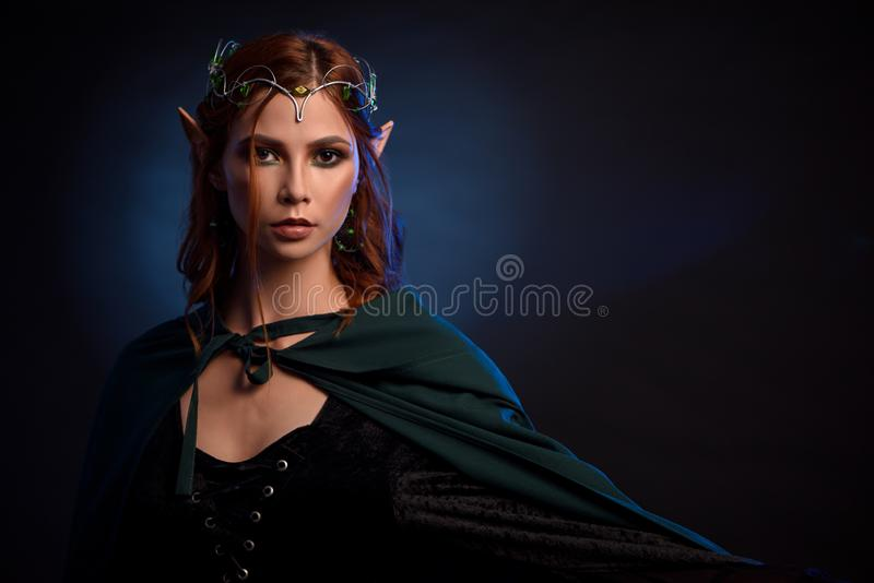 Charming queen of elves in silver tiara and red hair. Crop of young and beautiful woman in green cloak posing at camera. Charming queen of elves in silver tiara royalty free stock image
