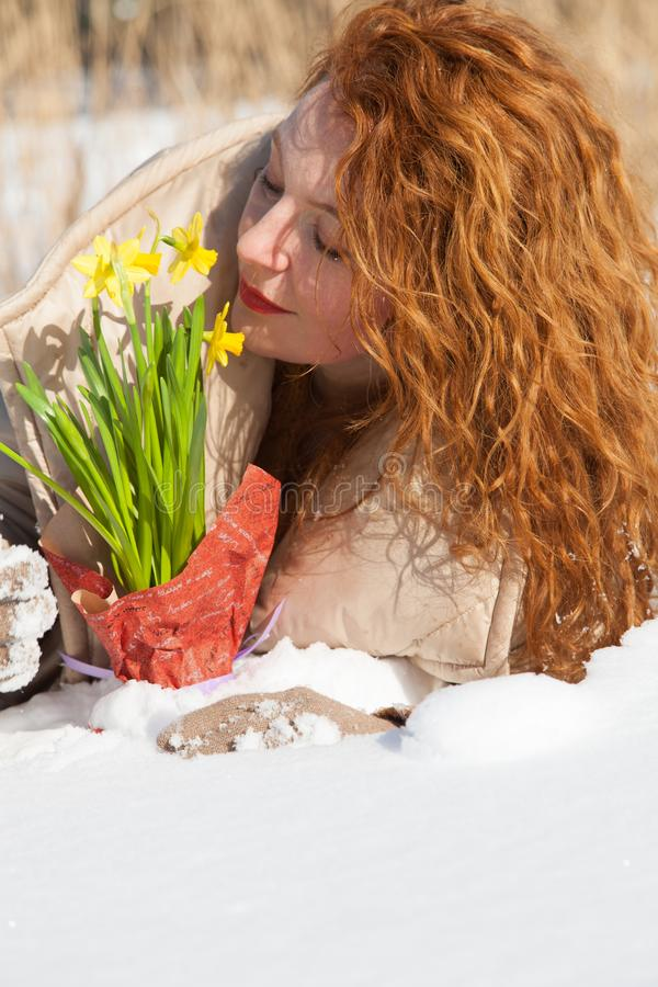 Charming red haired woman smelling yellow snowdrops while resting in snow royalty free stock image