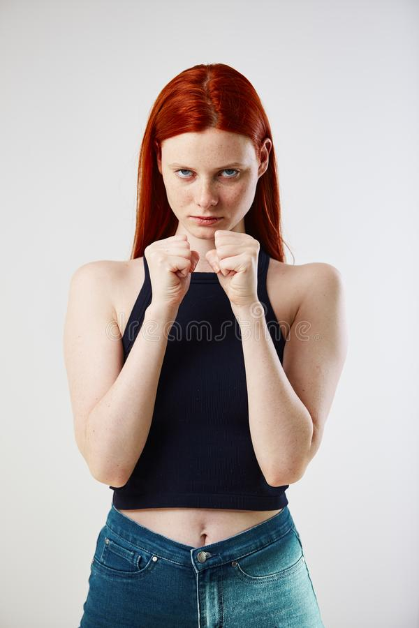 Charming redhead long-haired girl dressed in black top and jeans keeps hands in fists on the white background in the stock photos