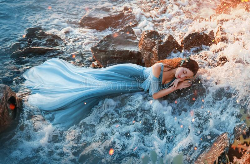 girl in blue long tender dress sweetly sleeps in cold water of waterfall royalty free stock images