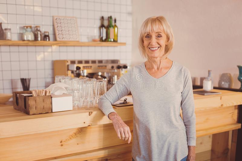 Charming senior cafe owner posing near counter stock photography